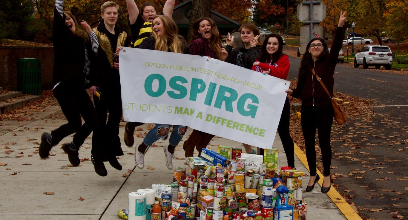 people jumping with OSPIRG sign in front of pile of canned food